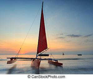 Red sailboat on the beach with a beautiful sunset