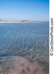 Red sand clear seas and beach umbrellas