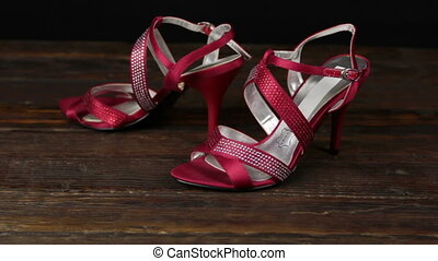 Red sandals with high heels on a wooden background. Zoom