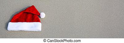 Red Santa Claus hat on caribbean beach.