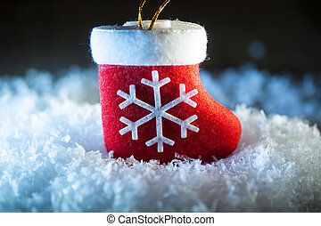 Red Santa's boot with snowflake in snow
