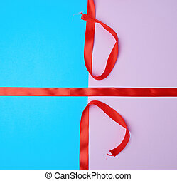 red satin ribbon on a colored background