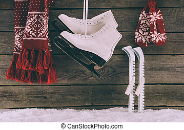 red scarf with gloves and white skates hanging on wooden wall