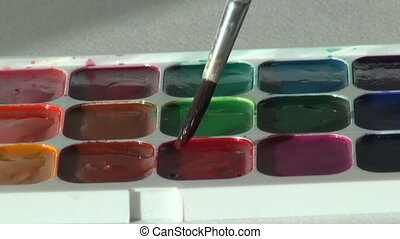 red scarlet ruddy color. close up. Artist works with brush...