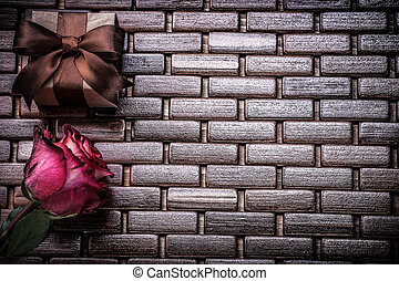 Red scented rose giftbox on wicker wooden place matting