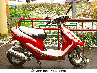 red scooter bike covered with first snow