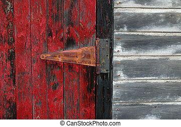 Rustic red door with hinge and peeling paint on a faded white shed