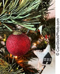 Red shiny ball hanging on the Christmas tree close-up.