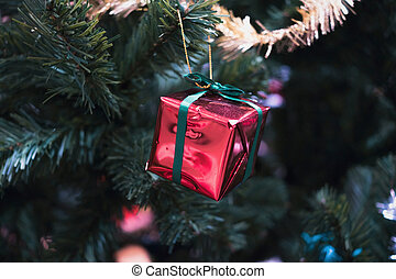 Red shiny gift on christmas tree