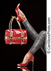 Female model's long legs wearing red high heel shoes and a purse/handbag hanging on the heels.