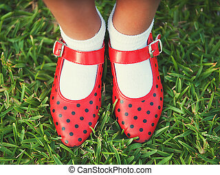 Red shoes with polka dots on a background of grass