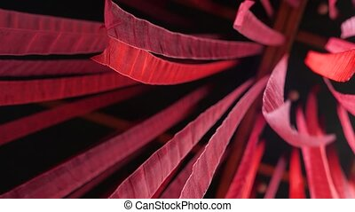 Ribbons fluttering on black background. Black background with red color lines. Red nailon stripes. Conceptual romantic decoration. Decorative red stripes, waving gently. View from below