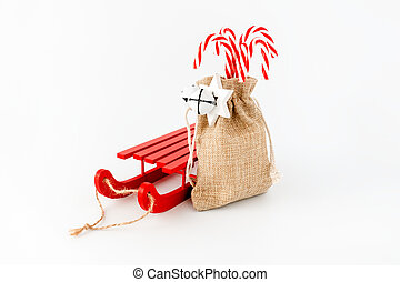 Red Sledge and Candy Canes in Jute Sack isolated on White
