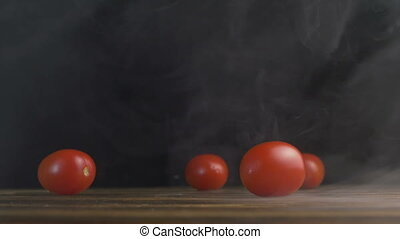 Red small tomatoes or Cherry tomato roll across the table in...