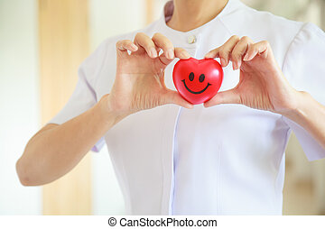 Red smiling heart held by female nurse's both hands, representing giving effort high quality service mind to patient. Professional, Specialist in white uniform concept