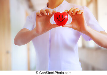 Red smiling heart held by female nurse's hand, representing giving effort high quality service mind to patient. Professional, Specialist in white uniform concept