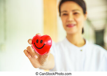 Red smiling heart held by smiling female nurse's hand, representing giving effort high quality service mind to patient. Professional, Specialist in white uniform concept