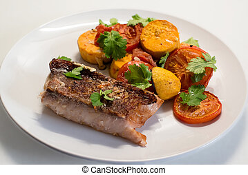 Fresh Red Snapper filet on the plate with tomatoes and potatoes