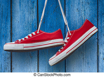 red sneakers hanging on a wooden blue background