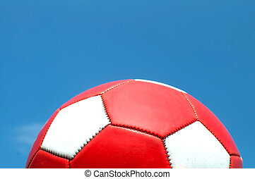 Red soccer ball with white dots against a blue sky