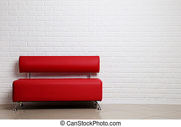 Red sofa on a brick wall background