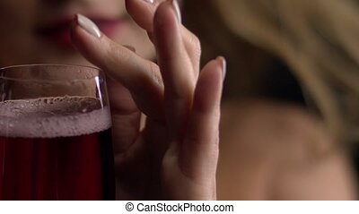 Red sparkling wine filling a glass. Slow motion. Women drinking a glass of red wine Black background