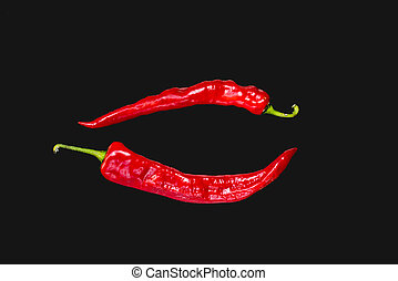 Red spicy chili peppers on black