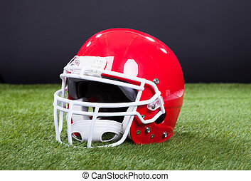 Red Sports Helmet Lying On Green Grass Field