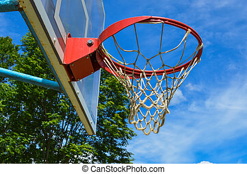 Red sports round basketball basket for playing basketball streetball on an open street area under the open sky with a net against a blue sky and trees
