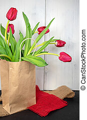 red spring tulips in brown paper sack