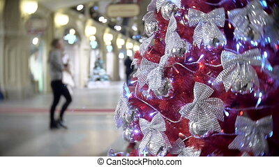Red spruce in silver bows. New Year's and abstract blurred shopping mall background with Christmas tree decorations.