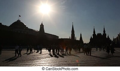 Red Square silhouette view against sun with tourists walking...