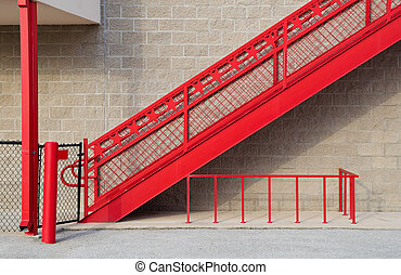 Red staircase against stone wall