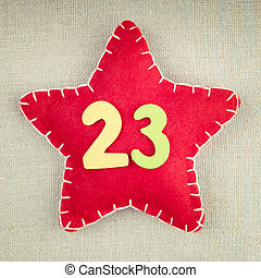Red star with wooden number 23 on vintage fabric background