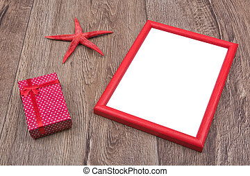Red starfish, gift and photo frame on a wooden background
