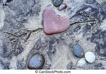 red stone heart, sea stone in the shape of a heart on the ...