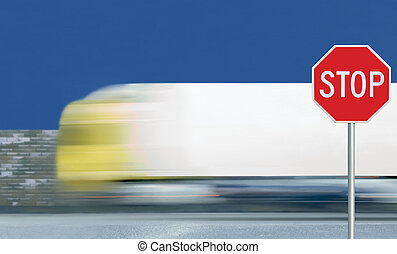 Red stop road sign, motion blurred truck vehicle traffic background, give way regulatory warning signage octagon, white octagonal frame, metallic pole post, blue summer sky