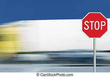 Red stop road sign, motion blurred truck vehicle traffic in background, regulatory warning signage octagon, white octagonal frame, metallic pole post