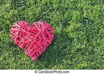 Red straw heart on the grass. Valentine's Day.