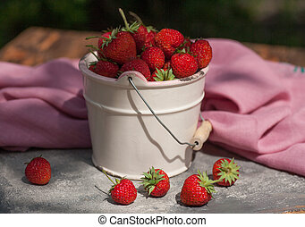 Red strawberies in a white bowl on the blue stone table
