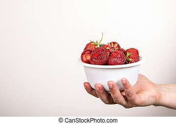 Red strawberries from organic farm in white bowl on white background. Summer delicacy
