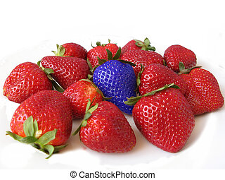 Red strawberries with a blue one. Difference and unique...