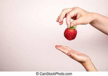 Red strawberry in hand on a white background. Healthy eating