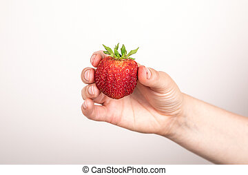 Red strawberry in hand on white background. Summer delicacy and vitamins
