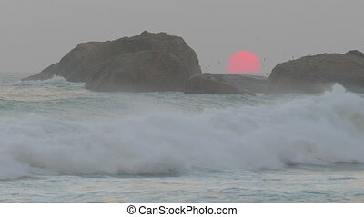 red sun is setting in sea between rocks