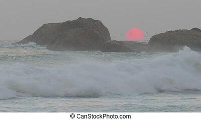 red sun is setting in sea between rocks