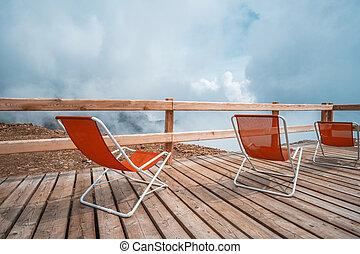 Red sunbeds in cloudy Alps - Red sunbeds standing on wooden ...