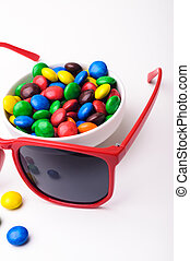 Red sunglasses and colorful candys. - Red sunglasses and...