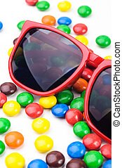 Red sunglasses and many colorful round candys. - Red...