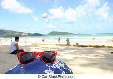 Red sunglasses at the beach, summer time